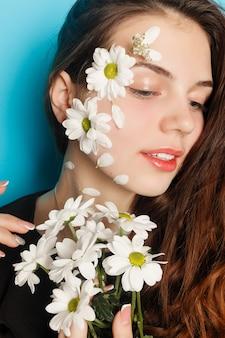 녹색 눈을 가진 아름다운 브루네트 소녀가 화장을 하고 꽃, 피부 관리 개념, 뷰티 스파, 바이오 제품으로 붉은 배경에서 포즈를 취하는 신선한 피부. 수평
