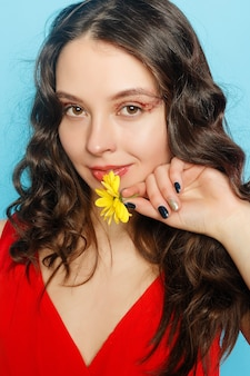 Beautiful brunette girl with green eyes make up and fresh skin posing at blue background with flower, skin care concept, beauty spa, bio product. horizontal