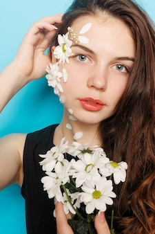 Beautiful brunette girl with green eyes make up and fresh skin posing at red background with flower, skin care concept, beauty spa, bio product. horizontal