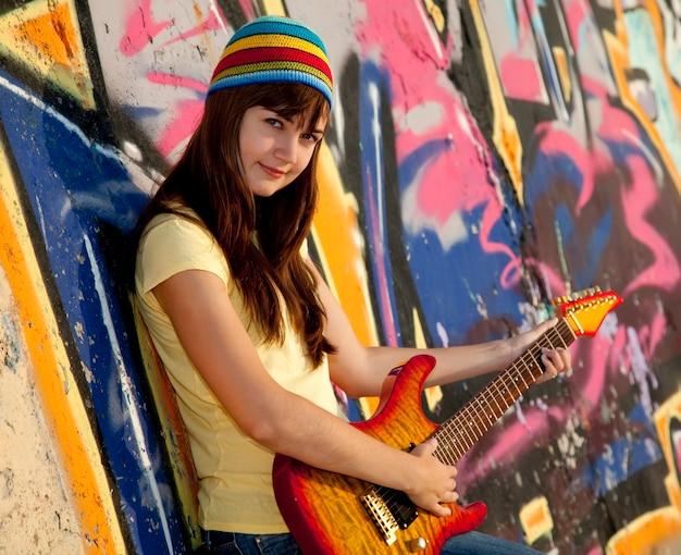 기타와 낙서 벽과 아름 다운 갈색 머리 소녀