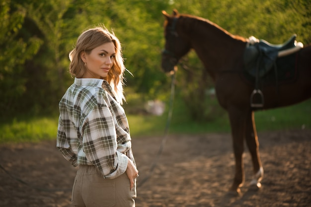Beautiful brunette girl with her horse outdoors