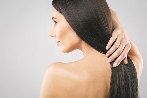 Красивая девушка брюнет с длинными и прямыми каштановыми волосами.