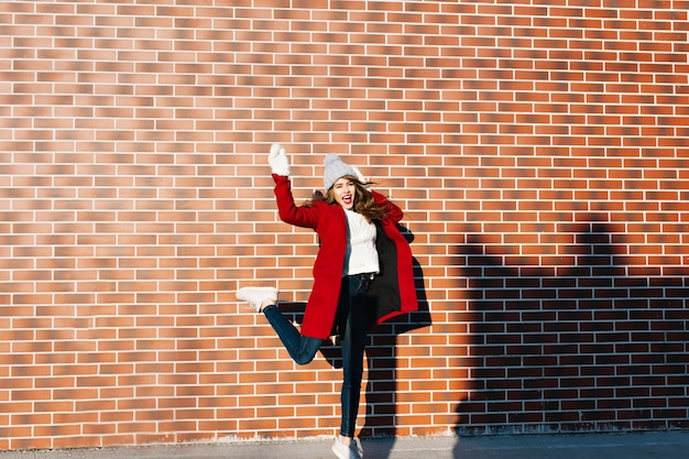 Beautiful brunette girl with long hair having fun on wall  outside. she wears red coat, white gloves and knitted hat.