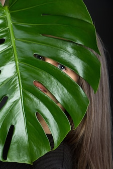 Beautiful brunette girl with long hair looks through monstera leaf on black