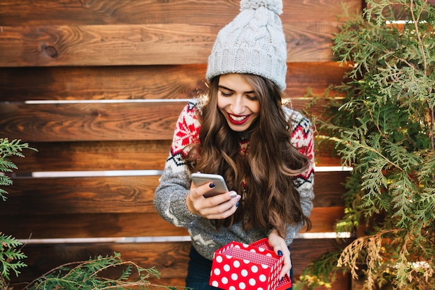 Beautiful brunette girl with long hair and red lips on wooden  outdoor. she wears knitted hat, holding phone and present box. she looks happy.