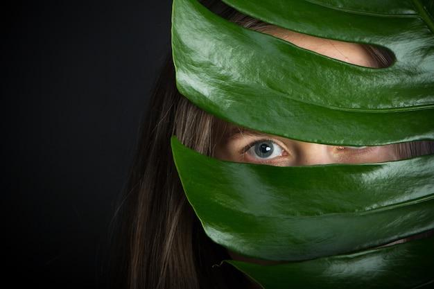 Красивая брюнетка девушка с длинными волосами с ярко-зеленой тропической веткой, девушка смотрит сквозь лист монстеры на черном фоне