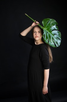 Beautiful brunette girl with long hair with bright green tropical branch, girl with monstera leaf on black background