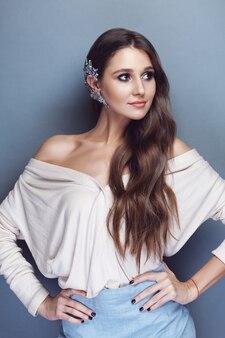 긴 물결 모양의 머리와 그녀의 귀에 크리스탈 커프와 아름다운 갈색 머리 소녀