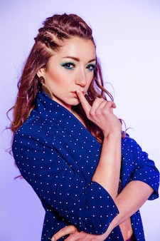 Beautiful brunette girl with make-up in blue tones, pigtails and a blue jacket posing on a background of purple. vertycal photo
