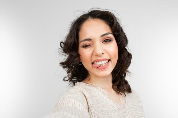 化粧をしている美しいブルネットの少女は顔をゆがめながら自分撮りを取ります