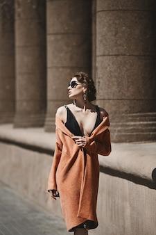 검은 세련된 드레스, 트렌디 한 코트와 도시 거리에서 포즈를 취하는 세련된 선글라스에 섹시한 몸매를 가진 아름다운 갈색 머리 소녀