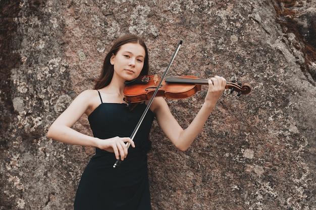 Красивая девушка брюнет со скрипкой на скале. фото высокого качества