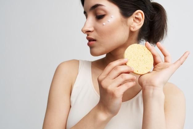 Красивая брюнетка держит губку в руках крупным планом чистой здоровой кожи