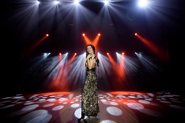 밝은 빛을 가진 무대에서 긴 드레스에 아름 다운 갈색 머리. 어두운 빨간색 배경, 연기, 콘서트 스포트 라이트.