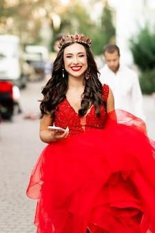 Красивая брюнетка в красном платье с короной. улыбающаяся девушка брюнет с крупным планом телефона. фон дикая природа, солнечный свет, сочная трава. художественное фото. свадебная фотосессия