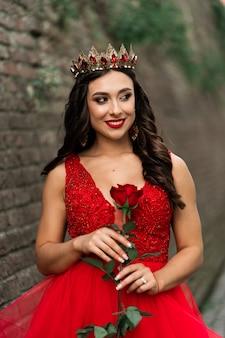 Красивая брюнетка в красном платье с короной. брюнетка девушка с одной красной розой снаружи на каменной стене чердака