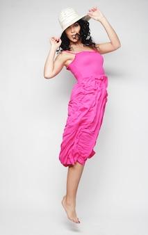 Красивая брюнетка в розовом платье с прыжками в шляпе