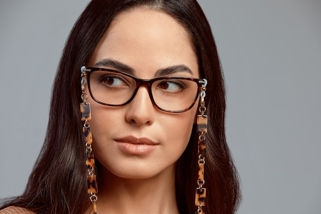 灰色の背景にスタイリッシュなメガネの美しいブルネット、完璧なメイク、美しい健康な肌、灰色の背景、コピースペースのメガネの女性。