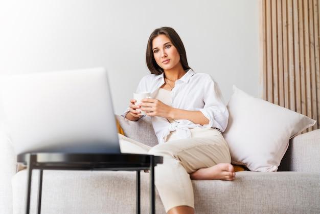 Красивая брюнетка в белой рубашке сидит на софе, держа в руке белую чашку с горячим кофе.