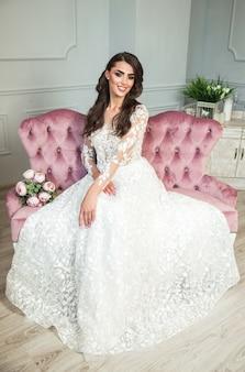 エレガントな高価なインテリアで豪華なウェディングドレスで美しいブルネットの女性。ブライダルブーケを持って白いウェディングドレスでかなり若い花嫁。ウェディングドレスの豪華な花嫁。髪型・美容