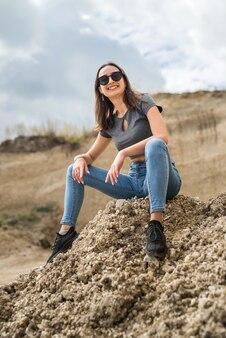 砂の採石場で美しいブルネットの女性はリラックスして晴れた夏の日に彼女の時間を楽しんでください