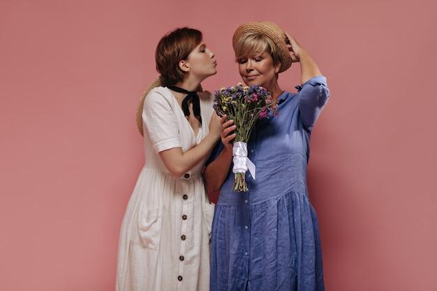 キスを吹いて、孤立した背景に野生の花と青いドレスと帽子の老婆とポーズをとって白い服を着た美しいブルネットの女性。