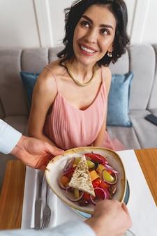 カフェワーカーを見て、おいしいサラダのプレートを保持している男性が笑っている美しいブルネットの女性