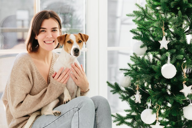 Beautiful brunette lady smiles happily, spends free time with favourite pet celebrate