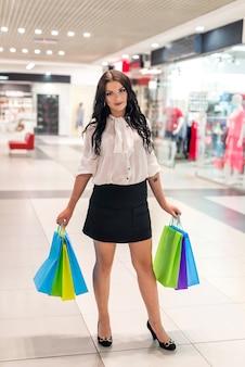 モールで買い物袋を持つ美しいブルネットの女性