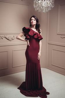 Beautiful brunette in a long dress in a classic light interior