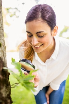 Beautiful brunette looking at plant through magnifying glass