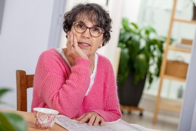 Beautiful brunette mature woman dressing in pink reading  newspaper