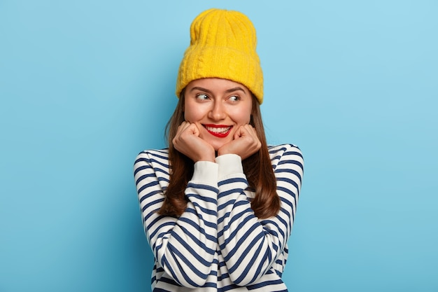 Beautiful brunette millennial woman keeps hands under chin, bites lips, has satisfied expression, wears yellow hat and striped jumper