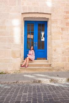 花の花束を保持しているファッショナブルなピンクのドレスの美しいブルネットモデル。ドアに座っている女性。
