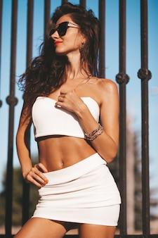 夏の白いタンクトップとスカートの美しいブルネットモデル。女性が鉄の柵の近くの通りでポーズします。