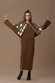 長い茶色のベルベットのドレスでフルハイトをポーズする美しいブルネットのモデル。