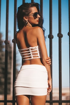 Beautiful brunette model in summer white tank top and skirt. woman posing in the street near iron fence.