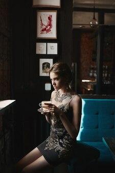 カフェのインテリアで彼女の手にコーヒーのカップと黒と金のカクテルドレスの美しいブルネットモデルの女性