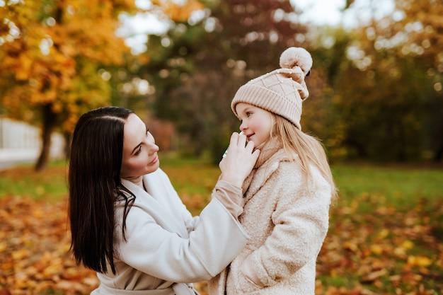 美しいブルネットのお母さんは秋の公園で帽子とスカーフで小さな娘の鼻にスプレーを埋めます