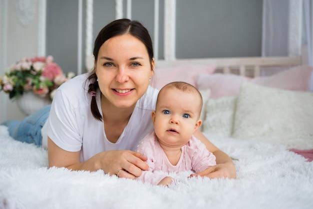 흰색 티셔츠에 아름 다운 갈색 머리 엄마는 침대에 누워 핑크 드레스에 그녀의 아기 딸을 안아