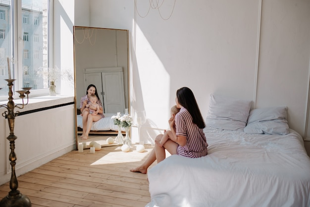 Красивая брюнетка мама в пижаме сидит на кровати в комнате и смотрит в большое зеркало