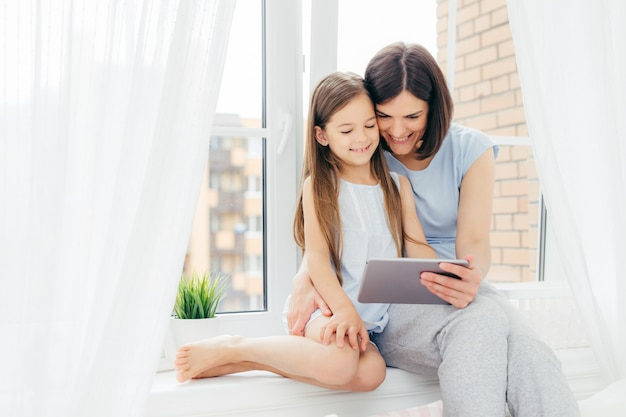 Beautiful brunette mother and daughter spend free time together, sit on window sill, watch interesting movie via digital tablet