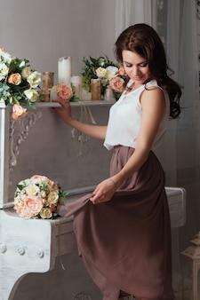 Beautiful brunette near the old piano on which lay bouquets of roses