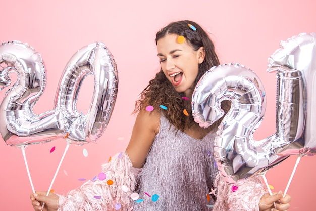 Beautiful brunette party girl with curly hair and festive clothes posing on a pink studio background with confetti and holding silver balloons for the new year concept