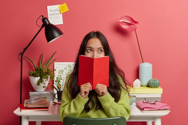 Beautiful brunette pensive mixed race female student learns information from textbook, covers half of face with red diary