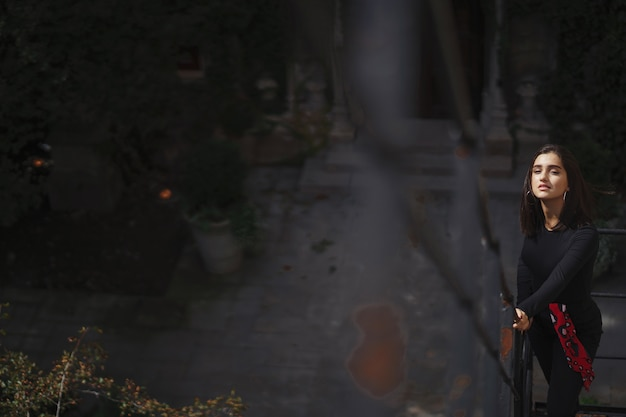 검은 계단에 포즈를 취하는 아름 다운 갈색 머리