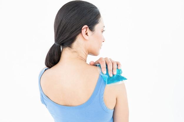 Beautiful brunette putting gel pack on shoulder