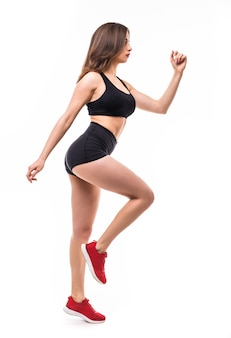 Beautiful brunette sexy woman in black sportswear does exercises for strong figure body
