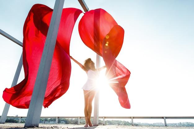 Bella ballerina bruna con tende rosse in posa sul tetto
