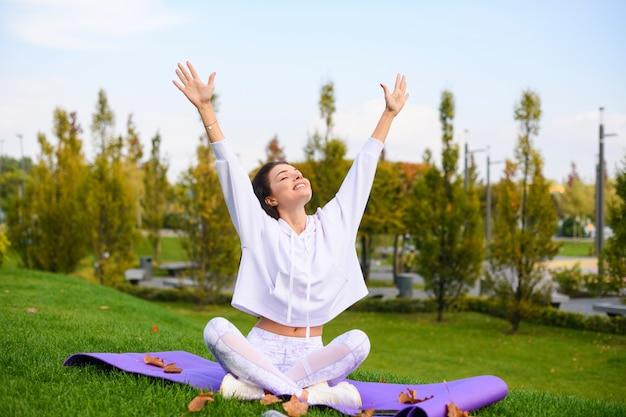 美しいブルネットは蓮のポーズでスポーツマットに座り、トレーニング、ストレッチ、都市公園でのヨガ中に目を閉じて手を上げます